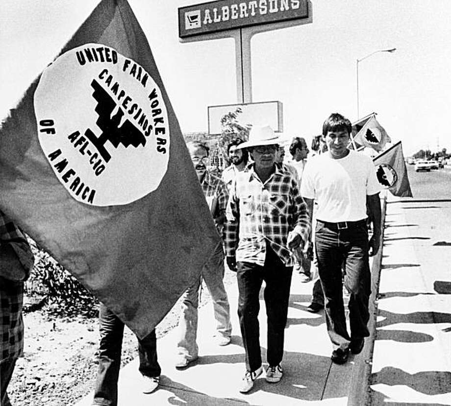Cesar Chavez, in plaid shirt, marches with members of the United Farm Workers outside a Delano, Calif., supermarket in protest of the sale of products not harvested by their union, Aug. 25, 1975. Photo: AP Photo/Walter Zeboski