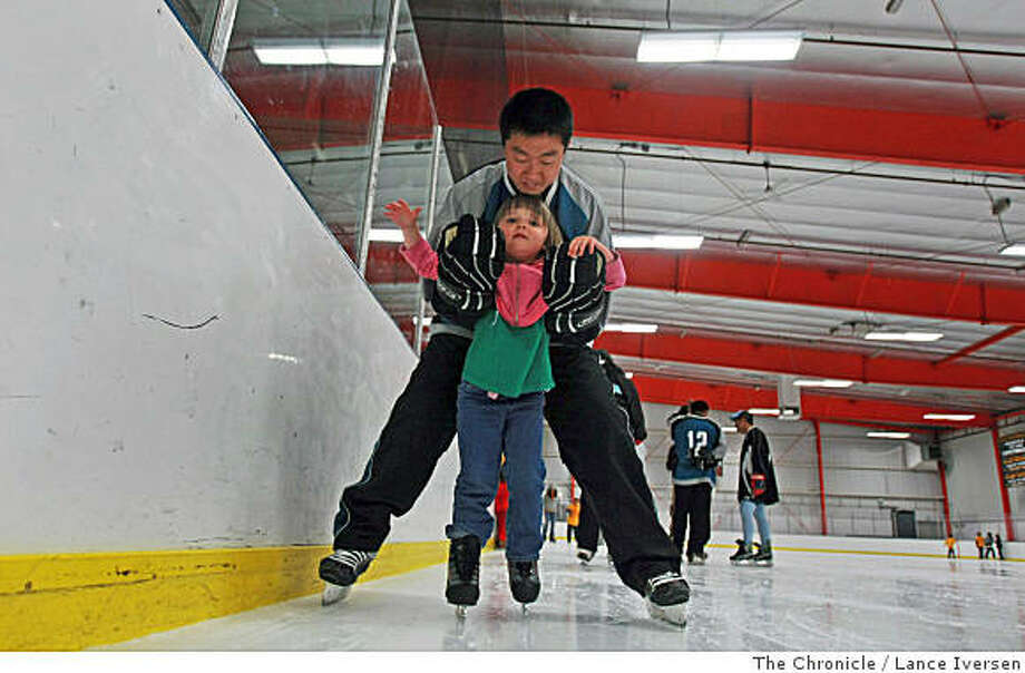 Liu Heenan, a member of the National Chinese Hockey team, the China Sharks, helps Barry Fong, age 4, from Oakland, Calif, around the ice at Oakland's Ice Center on Saturday, July 19, 2008. Members and coaches volunteered their Saturday afternoon to help Bay Area children learn the sport of ice skating. .Photo by Lance Iversen / The Chronicle Photo: Lance Iversen, The Chronicle