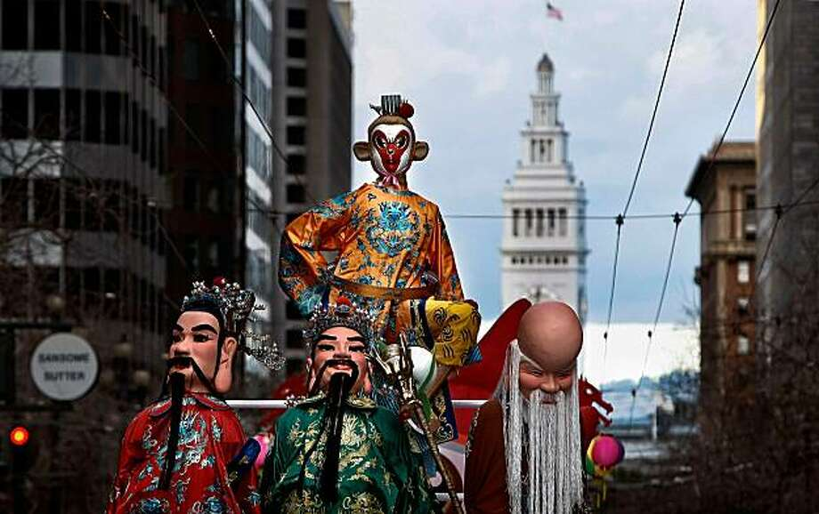 Parade - 5:01 p.m. - San Francisco.   I was covering the Chinese New Year parade up Market Street, I liked the contrast between the Ferry Building and a float filled with Chinese characters moving up the street.  Camera settings: ISO 200, f6.3, 1/160, 200mm lens, Canon 1D MkIII Photo: Michael Macor, The Chronicle