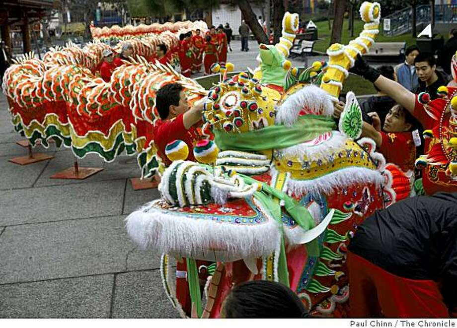 Volunteers tend to a blindfolded Gum Lung, the Chinese New Year Parade dragon, before the 238-foot-long serpent is awakened in an eye-dotting ceremony by Taoist priests at Portsmouth Square in San Francisco, Calif., on Saturday, Jan. 24, 2009. Photo: Paul Chinn, The Chronicle