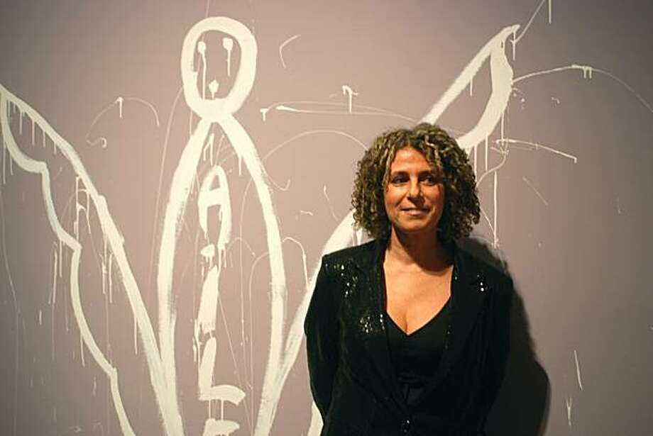 "Linda Ellia, the artist, stands beside her signature, a depiction of an angel with ""AILE"" written inside. The signature evolved when, to remain anonymous amongst the other participants, Ellia began signing her name as ""She,"" or, in French, ""Elle."" Phonetically it reads the same as the homonym ""Aile"" meaning ""wings,"" which she felt the project had given her to fly beyond her suffering. She also discovered, to her delight, that ""Aile"" is her last name backwards. Photo: Chloe Roth, The Chronicle"