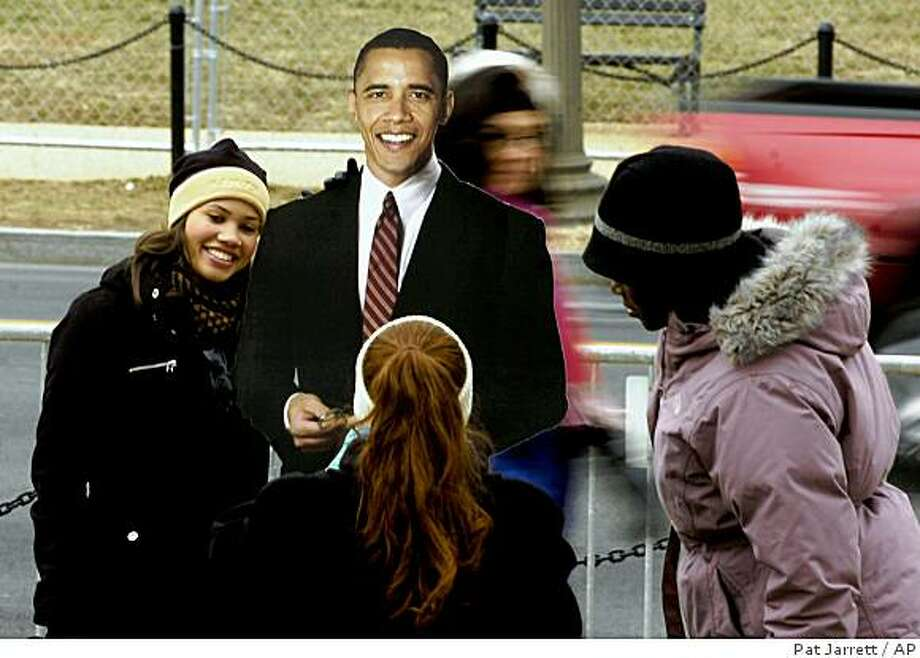 "A pedestrian has her photo taken with an Obama cut-out  in Washington, Sunday, Jan. 18, 2009.   Several hundred thousand people gathered on the National Mall on Sunday, during the "" We Are One: Opening Inaugural Celebration at the Lincoln Memorial. Photo: Pat Jarrett, AP"
