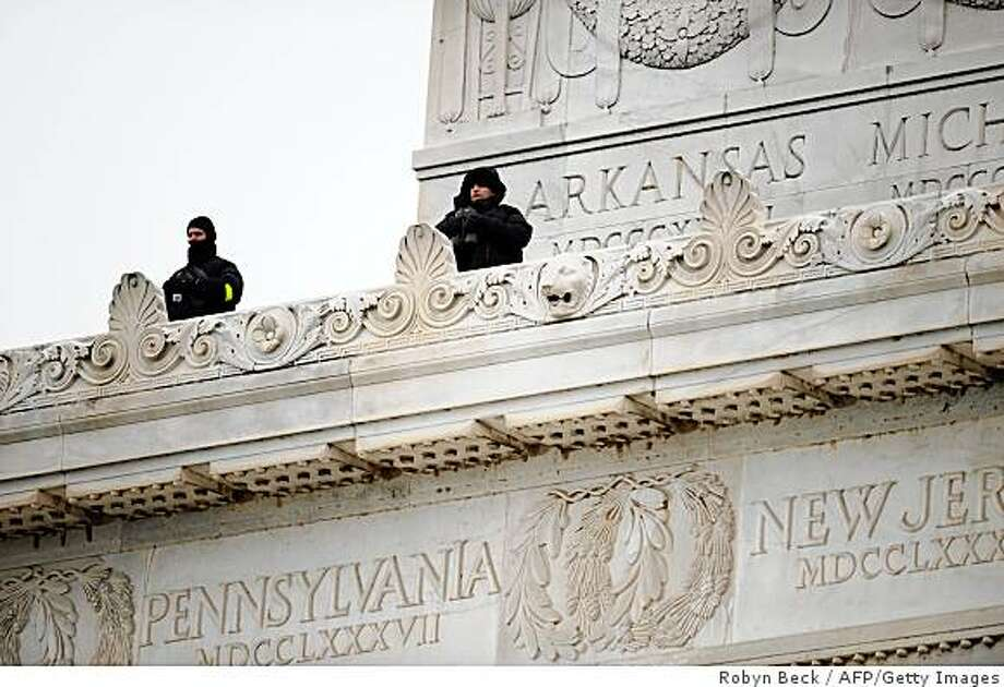 "Security agents watch the crowd from atop the Lincol Memorial at the 'We Are One"" concert, one of the events of US president-elect Barack Obama's inauguration celebrations, at the Lincoln Memorial in Washington on January 18, 2009. Photo: Robyn Beck, AFP/Getty Images"