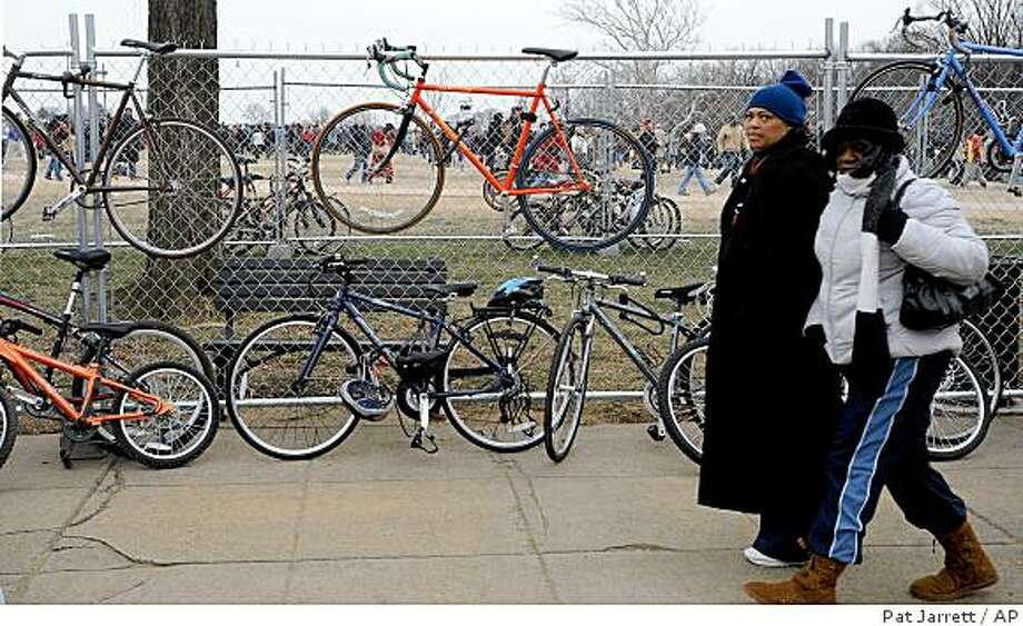 "Two women walk past bicycles that are locked to a fence along Constitution Ave in Washington, Sunday, Jan. 18, 2009.   Several hundred thousand people gathered on the National Mall on Sunday, during the "" We Are One: Opening Inaugural Celebration at the Lincoln Memorial. Photo: Pat Jarrett, AP"