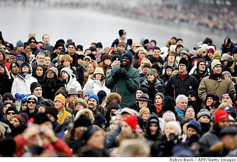 "People bundled up against the cold watch the 'We Are One"" concert, one of the events of US president-elect Barack Obama's inauguration celebrations, at the Lincoln Memorial in Washington on January 18, 2009. Photo: Robyn Beck, AFP/Getty Images"
