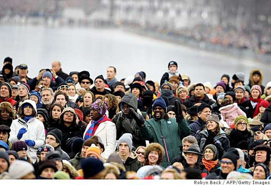 """People bundled up against the cold watch the 'We Are One"""" concert, one of the events of US president-elect Barack Obama's inauguration celebrations, at the Lincoln Memorial in Washington on January 18, 2009. Photo: Robyn Beck, AFP/Getty Images"""