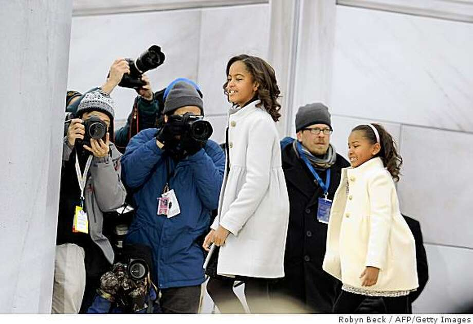 "US president-elect Barack Obama's daughter Malia (L) and Sasha (R) walk past a group of photographers as they arrive at the 'We Are One"" concert, one of the events of Obama's inauguration celebrations, at the Lincoln Memorial in Washington on January 18, 2009. Photo: Robyn Beck, AFP/Getty Images"