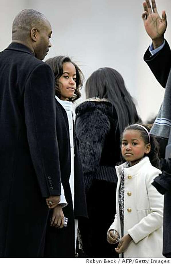"US president-elect Barack Obama's daughter Malia (L) and Sasha (R) attend the 'We Are One"" concert, one of the events of Obama's inauguration celebrations, at the Lincoln Memorial in Washington on January 18, 2009. Photo: Robyn Beck, AFP/Getty Images"