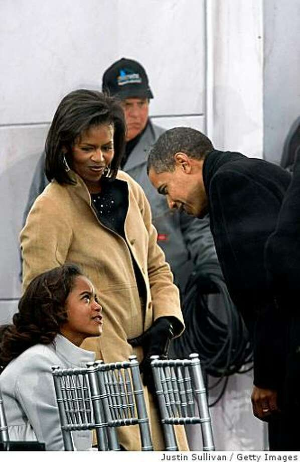"U.S. President-elect Barack Obama speaks with daughter Malia as his wife Michelle looks on during the ""We Are One: The Obama Inaugural Celebration At The Lincoln Memorial"" on January 18, 2009 at the National Mall in Washington, DC. The event includes a diverse array of talent featuring both musical performances and historical readings and an appearance by U.S. President-elect Barack Obama. Photo: Justin Sullivan, Getty Images"