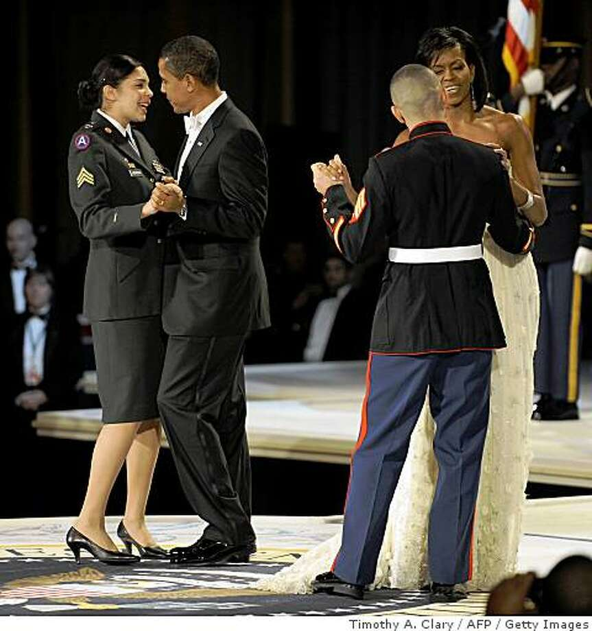 President Barack Obama dances with Army Sgt Margaret Herrera and his wife Michelle dance Marine Sgt Eliidio Guellen  during the Commander in Chief's Ball at the National Building Museum in Washington January 20 2009 . Photo: Timothy A. Clary, AFP / Getty Images
