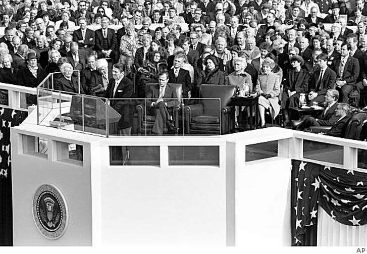 President Reagan delivers his inaugural address after being sworn in at the Capitol, Tuesday, January 20, 1981. From right, are: outgoing Vice President Walter Mondale; outgoing President Jimmy Carter; Reagan's son Ronald and his wife, Doria; Reagan's wife Nancy; Barbara Bush, wife of Vice President George Bush. Bush sits at center with his legs crossed; Sen. Mark Hatfield, R-OR, is behind Bush. Visible over the microphones are House Speaker Thomas P. O'Neill, D-MA, first row, and Rep. John Rhodes,R-AZ, second row. (AP Photo)