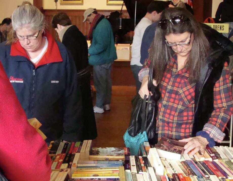 Cindy Weissman, left, of Fairfield, and Marcia Jones of Ridgefield sort though tables filled with trade paperbacks Saturday on the first day of the Pequot Library's annual Mid-Winter Book Sale. Photo: Meg Barone / Fairfield Citizen freelance