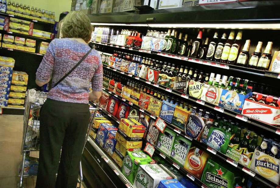 DES PLAINES, IL - MAY 09:  A woman peruses the beer cooler display in a grocery store May 9, 2006 in Des Plaines, Illinois. With new flavors and packaging, beer sales, reportedly, may be on the rise as it competes against wine, not only for shelf space, but also sales.  (Photo by Tim Boyle/Getty Images) Photo: Tim Boyle, Getty Images / 2006 Getty Images