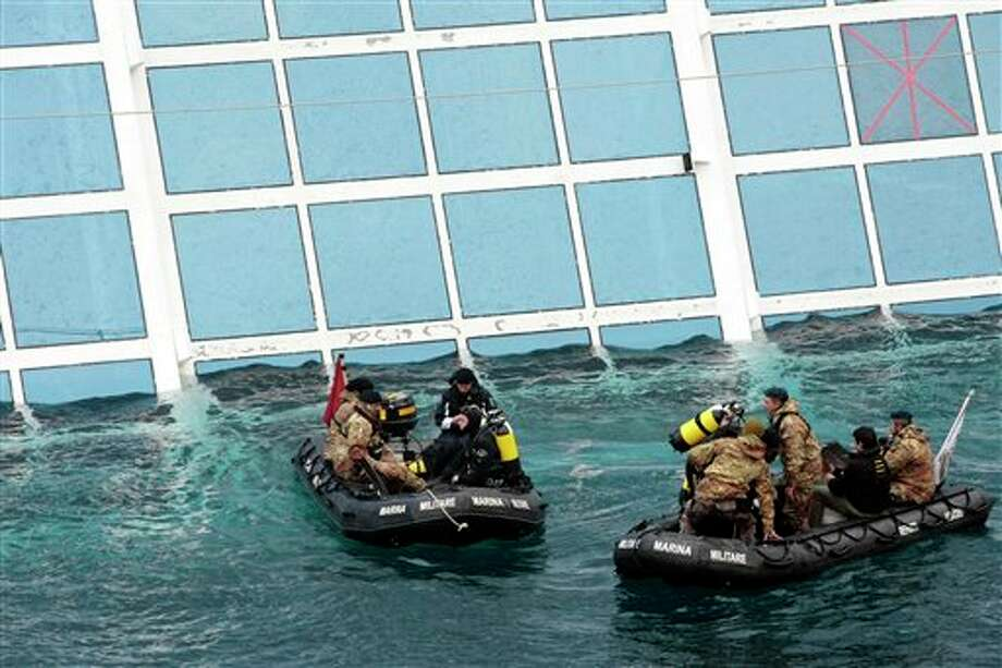 Italian Navy scuba divers approach the cruise ship Costa Concordia leaning on its side, after it ran  aground off the tiny Tuscan island of Giglio, Italy, Sunday, Jan. 15, 2012. A helicopter on Sunday airlifted a third survivor from the capsized hulk of a luxury cruise ship 36 hours after it ran aground off the Italian coast, as prosecutors confirmed they were investigating the captain for manslaughter charges and abandoning the ship. (AP Photo/Gregorio Borgia) Photo: Gregorio Borgia, Associated Press / AP