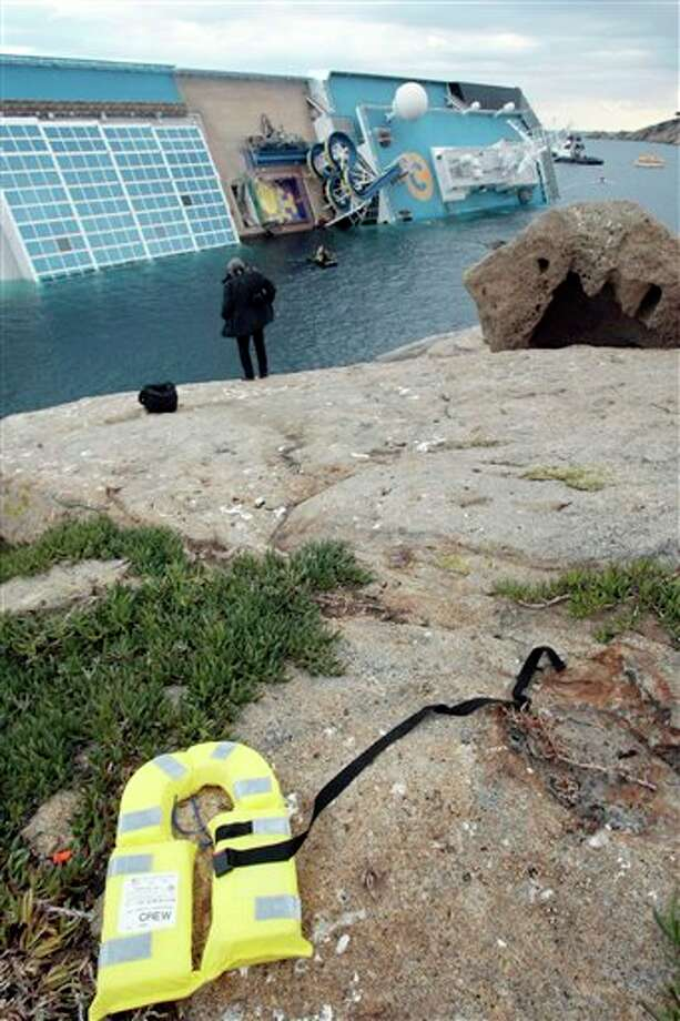 A life jacket lies on a rock near the stricken Costa Concordia cruise ship the day after it ran aground off the tiny Tuscan island of Giglio, Italy, Sunday, Jan. 15, 2012. A helicopter on Sunday airlifted a third survivor from the capsized hulk of a luxury cruise ship 36 hours after it ran aground off the Italian coast, as prosecutors confirmed they were investigating the captain for manslaughter charges and abandoning the ship. (AP Photo/Gregorio Borgia) Photo: Gregorio Borgia, Associated Press / AP