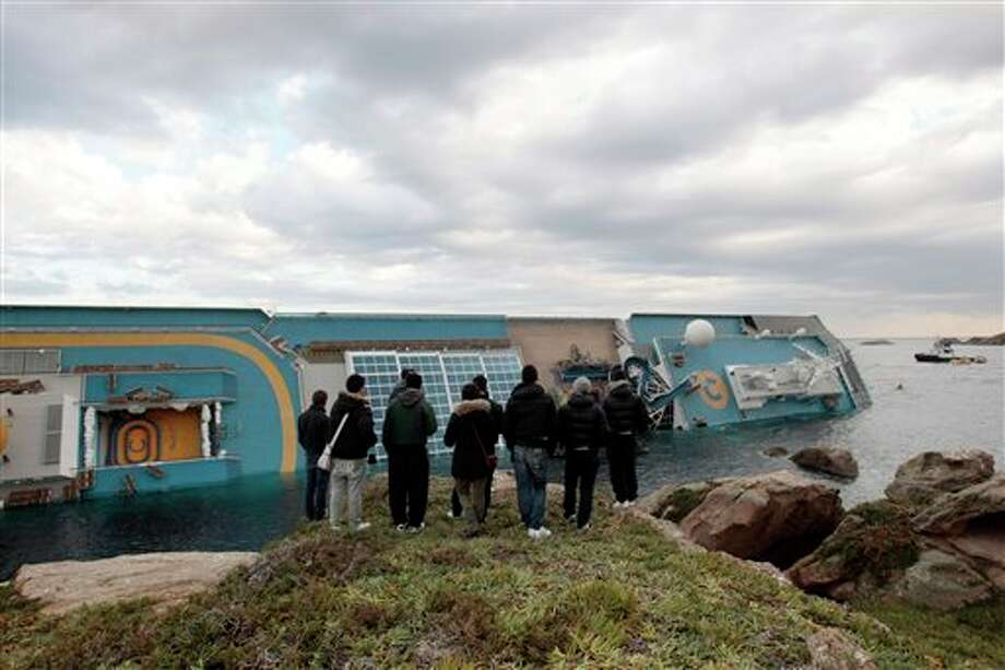 People stop and look the cruise ship Costa Concordia leaning on its side, after it ran  aground off the tiny Tuscan island of Giglio, Italy, Sunday, Jan. 15, 2012. A helicopter on Sunday airlifted a third survivor from the capsized hulk of a luxury cruise ship 36 hours after it ran aground off the Italian coast, as prosecutors confirmed they were investigating the captain for manslaughter charges and abandoning the ship. (AP Photo/Gregorio Borgia) Photo: Gregorio Borgia, Associated Press / AP