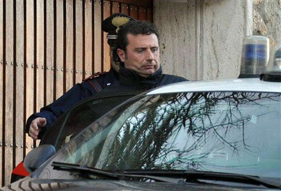 In this photo taken on Saturday, Jan. 14, 2012, Francesco Schettino  the captain of the luxury cruiser Costa Concordia, which ran aground off Italy's Tuscan coast, enters a Carabinieri car in Porto Santo Stefano, Italy. A helicopter on Sunday airlifted a third survivor from the capsized hulk of a luxury cruise ship 36 hours after it ran aground off the Italian coast, as prosecutors confirmed they were investigating the captain for manslaughter charges and abandoning the ship. (AP Photo/Enzo Russo) Photo: Enzo Russo, Associated Press / AP