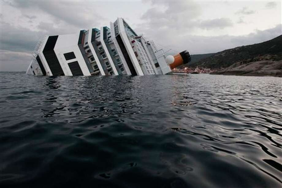 The cruise ship Costa Concordia leans on its side, after it ran aground off the tiny Tuscan island of Giglio, Italy, Sunday, Jan. 15, 2012. A helicopter on Sunday airlifted a third survivor from the capsized hulk of a luxury cruise ship 36 hours after it ran aground off the Italian coast, as prosecutors confirmed they were investigating the captain for manslaughter charges and abandoning the ship. (AP Photo/Gregorio Borgia) Photo: Gregorio Borgia, Associated Press / AP2012