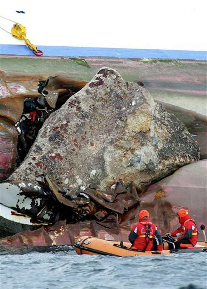 Firefighters on a dinghy look at a rock emerging from the side of the luxury cruise ship Costa Concordia, the day after it ran aground off the Tuscan island of Giglio, Italy, Sunday, Jan. 15, 2012. The Italian Coast Guard says its divers have found two more bodies aboard the stricken Costa Concordia cruise ship. The discovery of the bodies brings to five the number of known dead after the luxury ship ran aground with some 4,200 people aboard on Friday night. (AP Photo/Andrea Sinibaldi, Lapresse)   ITALY OUT Photo: Andrea Sinibaldi, Associated Press / PRESL