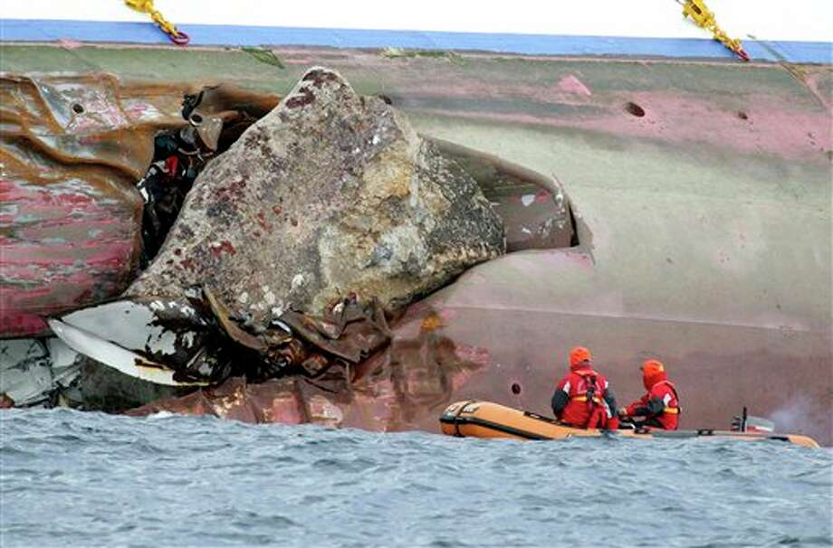 Firefighters on a dinghy look at a rock emerging from the side of the luxury cruise ship Costa Concordia, the day after it ran aground off the Tuscan island of Giglio, Italy, Sunday, Jan. 15, 2012.  The Italian Coast Guard says its divers have found two more bodies aboard the Costa Concordia. The discovery of the bodies brings to five the number of known dead after the luxury ship ran aground with some 4,200 people aboard on Friday night. (AP Photo/Andrea Sinibaldi, Lapresse)   ITALY OUT Photo: Andrea Sinibaldi, Associated Press / AP2012