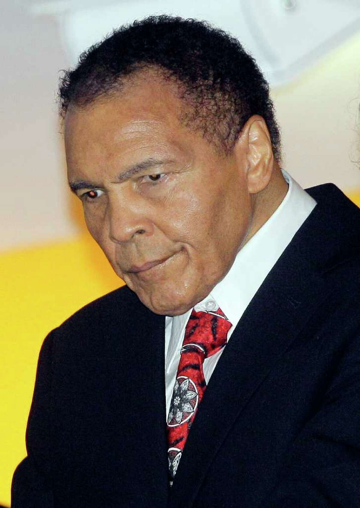Boxing great Muhammad Ali looks down from a balcony at friends while attending a celebration for his 70th birthday at the Muhammad Ali Center on Saturday, Jan. 14, 2012, in Louisville, Ky. Ali turns 70 Tuesday. (AP Photo/Mark Humphrey)