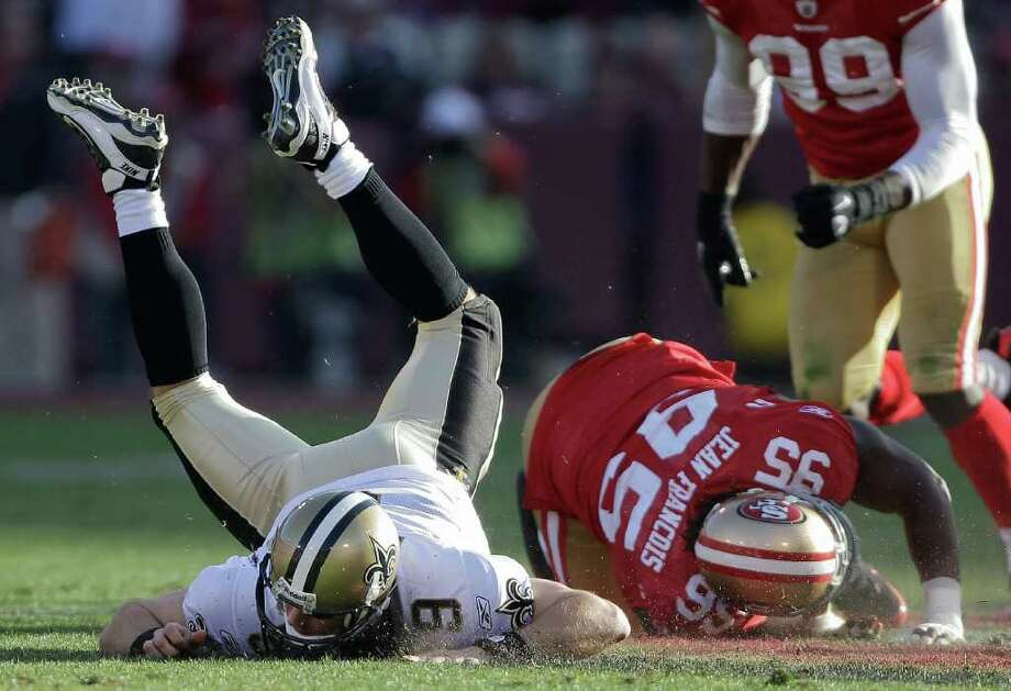 Saints quarterback Drew Brees (left) hits the ground thanks in part 49ers defensive tackle Ricky Jean-Francois. Photo: AP