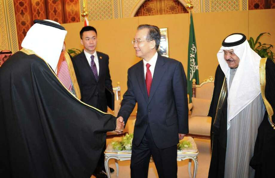 In this photo released by Saudi Press Agency, Chinese Premier Wen Jiabao, center, is welcomed by an unidentified Saudi official, left, as Saudi crown prince Nayef bin Abdel-Aziz, right, looks on prior their meeting in Riyadh, Saudi Arabia, Saturday, Jan. 14, 2012. China's premier visits Saudi Arabia as part of six-day Mideast trip that also takes him to the United Arab Emirates and Qatar. The visit to the region runs from Jan. 14-19. Wen Jiabao is slated to discuss the Arab Spring uprising and talks are likely to also focus on the latest U.S. sanctions on Iran, a major oil exporter to China. (AP Photo/HO) EDITORIAL USE ONLY, NO SALES Photo: HO / Saudi Press Agency