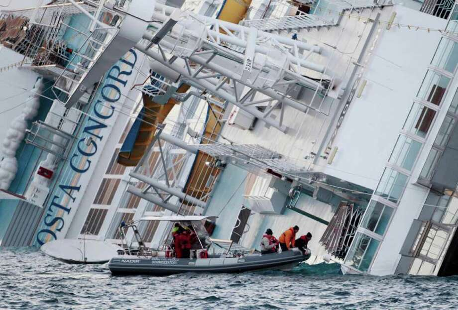 Emergency crews on Sunday approach the luxury cruise ship Costa Concordia, which ran aground off the tiny Tuscan island of Giglio, Italy. Divers found the bodies of two men still in their life jackets, bringing the death toll to five. Photo: Gregorio Borgia / AP