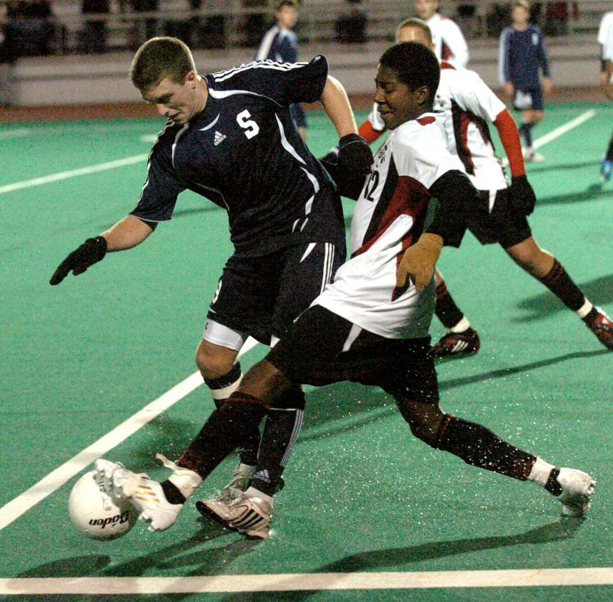 Central's #12 Shakir Terralonge, right, tries to get the ball away from Staples' #9 Brendan Lesch, during FCIAC soccer action in Bridgeport, Conn. on Wednesday Oct. 28, 2009. Central beat Staples 2-0.
