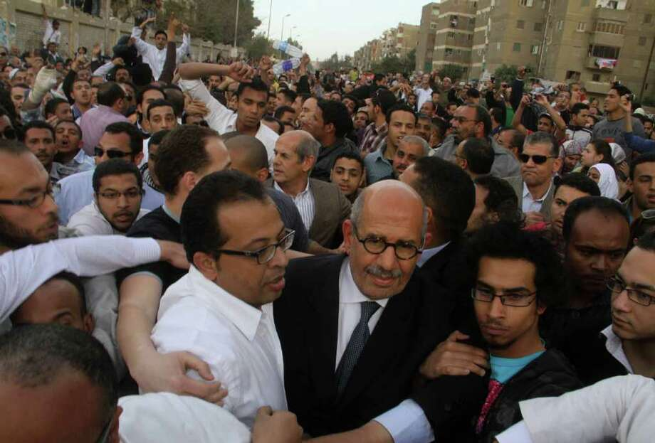 FILE - In this Saturday, March 19, 2011 file photo, supporters of Egyptian reform campaigner and Nobel laureate Mohamed ElBaradei, front center with dark jacket, try to protect him as angry protesters shout slogans as he arrives to cast his vote outside a polling center in Cairo's Mokkatam district, Egypt. With less than six months left for Egypt's ruling generals to hand over power, reform leader Mohammed ElBaradei's surprise pullout from the presidential race has laid bare the messiness of what was supposed to be a transition to democracy after the uprising a year ago. (AP Photo/Ahmed Ali, File) Photo: Amhed Ali / AP