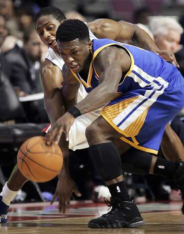 Detroit Pistons' Brandon Knight, left, tries to knock the ball away from Golden State Warriors' Nate Robinson during the second half of an NBA basketball game Sunday, Jan. 15, 2012, in Auburn Hills, Mich. The Warriors defeated the Pistons 99-91. (AP Photo/Duane Burleson) Photo: Duane Burleson, Associated Press