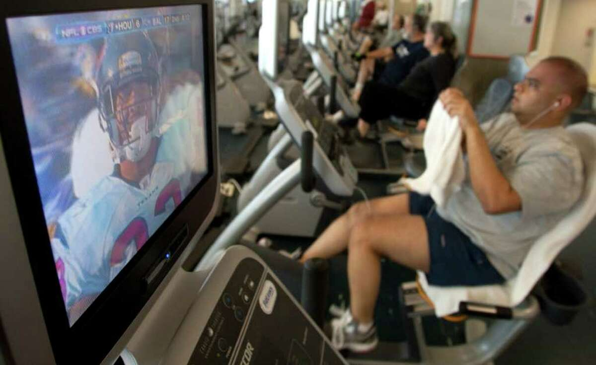 Amith Reddy proves he can multitask like a champ as he works out at the Tellepsen Family Downtown YMCA on Sunday while keeping track of how the Texans were doing in Baltimore.