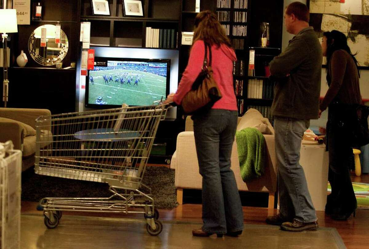 Sara McKay, left - with son Jason and daughter-in-law Sherry - spend some time catching up on how the big game is going while doing double duty by shopping at IKEA.