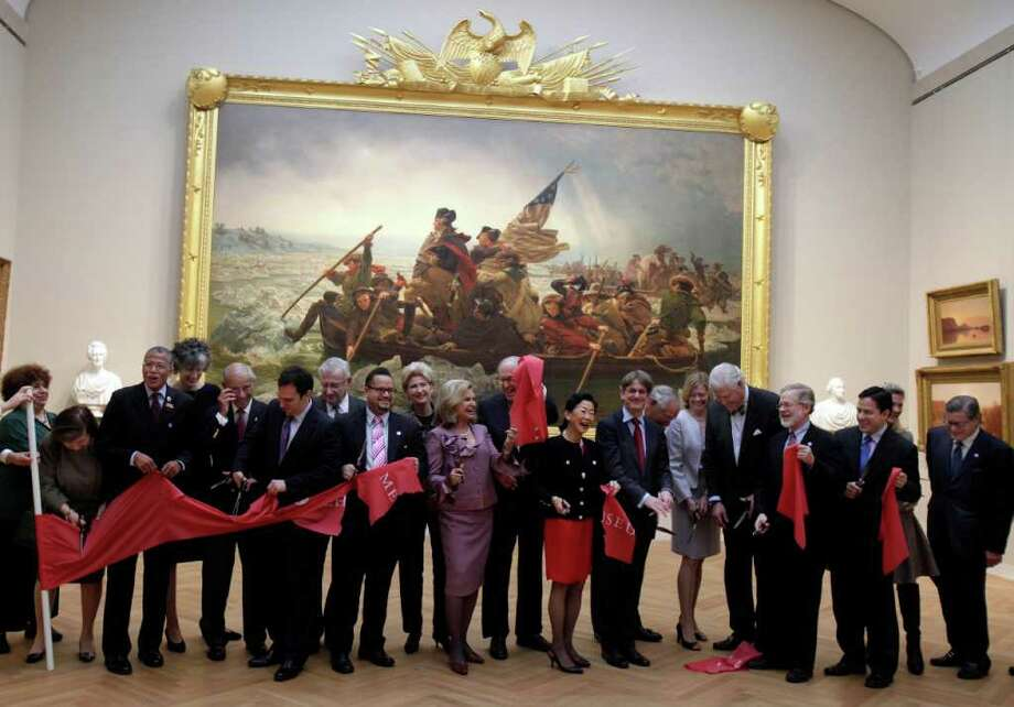 "In this Jan. 12, 2012 photo, Morrison Heckscher, center, the chairman of the American Wing at the Metropolitan Museum of Art in New York, raises his piece from the ceremonial ribbon cutting, in New York. The wing is scheduled to reopen Monday, Jan. 16, 2012, after its $100-million renovation. In background is the restored ""Washington Crossing the Delaware,"" by Emanuel Gottlieb Leutze. (AP Photo/Richard Drew) Photo: Richard Drew"