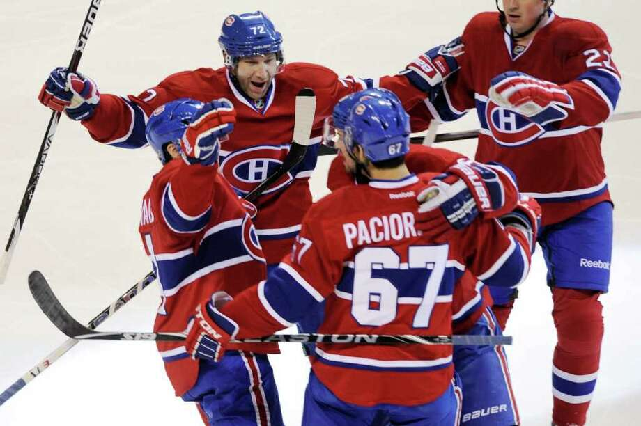 Montreal Canadiens' Max Pacioretty (67) celebrates with Erik Cole (72), David Desharnais, left, and Tomas Plekanec after scoring against the New York Rangers during the first period of an NHL hockey game, Sunday, Jan. 15, 2012, in Montreal. (AP Photo/The Canadian Press, Graham Hughes) Photo: Graham Hughes