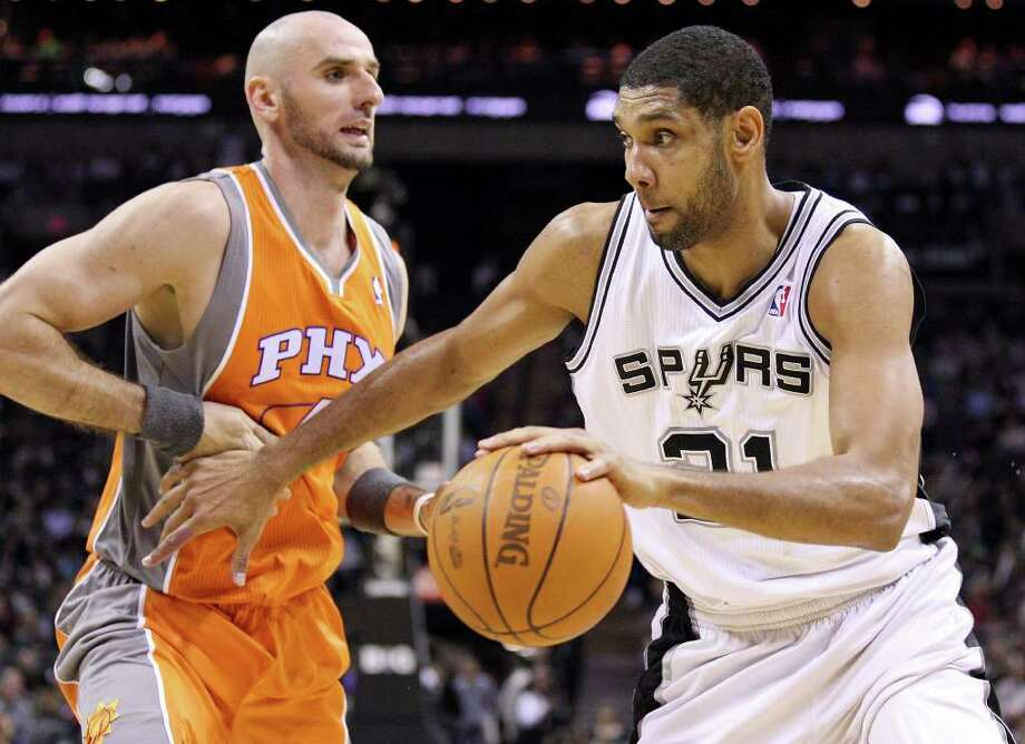 San Antonio Spurs' Tim Duncan drives around Phoenix Suns' Marcin Gortat during second half action Sunday Jan. 15, 2012 at the AT&T Center. The Spurs won 102-91. Photo: EDWARD A. ORNELAS, Express-News / SAN ANTONIO EXPRESS-NEWS (NFS)