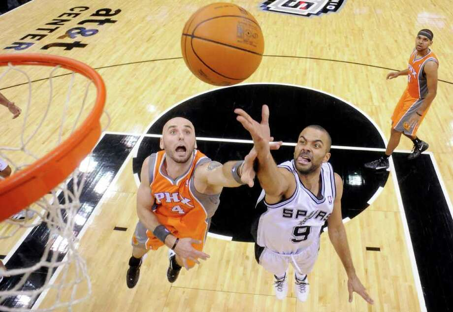 San Antonio Spurs' Tony Parker shoots around Phoenix Suns' Marcin Gortat during second half action Sunday Jan. 15, 2012 at the AT&T Center. The Spurs won 102-91. Photo: EDWARD A. ORNELAS, Express-News / SAN ANTONIO EXPRESS-NEWS (NFS)