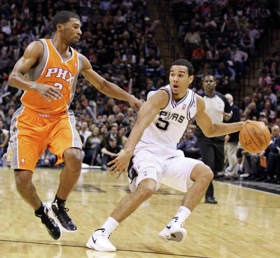 San Antonio Spurs' Cory Joseph looks for room around Phoenix Suns' Ronnie Price  during second half action Sunday Jan. 15, 2012 at the AT&T Center. The Spurs won 102-91. Photo: EDWARD A. ORNELAS, Express-News / SAN ANTONIO EXPRESS-NEWS (NFS)
