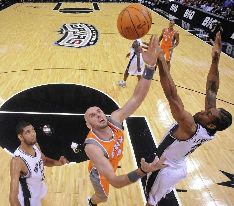 Phoenix Suns' Marcin Gortat shoots between San Antonio Spurs' Tim Duncan and San Antonio Spurs' Kawhi Leonard during first half action Sunday Jan. 15, 2012 at the AT&T Center. Photo: EDWARD A. ORNELAS, Express-News / SAN ANTONIO EXPRESS-NEWS (NFS)