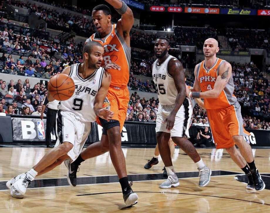 San Antonio Spurs' Tony Parker drives around Phoenix Suns' Channing Frye as San Antonio Spurs' DeJuan Blair  and Phoenix Suns' Marcin Gortat look on during first half action Sunday Jan. 15, 2012 at the AT&T Center. Photo: EDWARD A. ORNELAS, Express-News / SAN ANTONIO EXPRESS-NEWS (NFS)