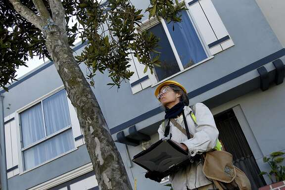Arborist Wendy Wilkins examines and inspects a swamp myrtle tree on Broad Street before putting a notice on the tree. With a dwindling budget, San Francisco's Dept. of Public Works plans to hand over the care of thousands of trees to residents who live nearby. A group of arborists are currently inspecting the health of the trees.