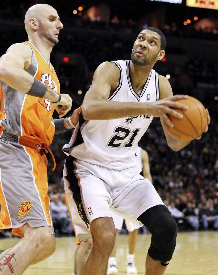 San Antonio Spurs' Tim Duncan looks for room around Phoenix Suns' Marcin Gortat during second half action Sunday Jan. 15, 2012 at the AT&T Center. The Spurs won 102-91. Photo: EDWARD A. ORNELAS, Express-News / SAN ANTONIO EXPRESS-NEWS (NFS)