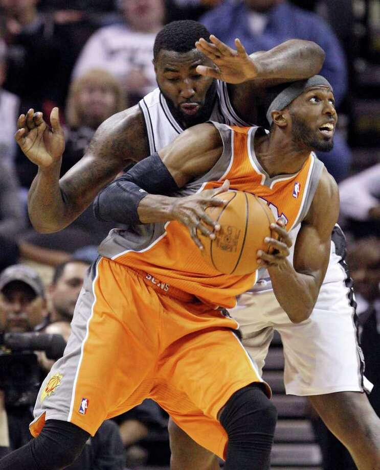 San Antonio Spurs' DeJuan Blair defends Phoenix Suns' Hakim Warrick during first half action Sunday Jan. 15, 2012 at the AT&T Center. Photo: EDWARD A. ORNELAS, Express-News / SAN ANTONIO EXPRESS-NEWS (NFS)