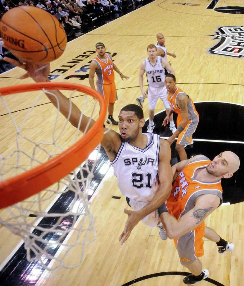 Spurs power forward Tim Duncan, who was 10 of 14 for 24 points, goes to the basket around Suns center Marcin Gortat. Photo: EDWARD A. ORNELAS / SAN ANTONIO EXPRESS-NEWS (NFS)
