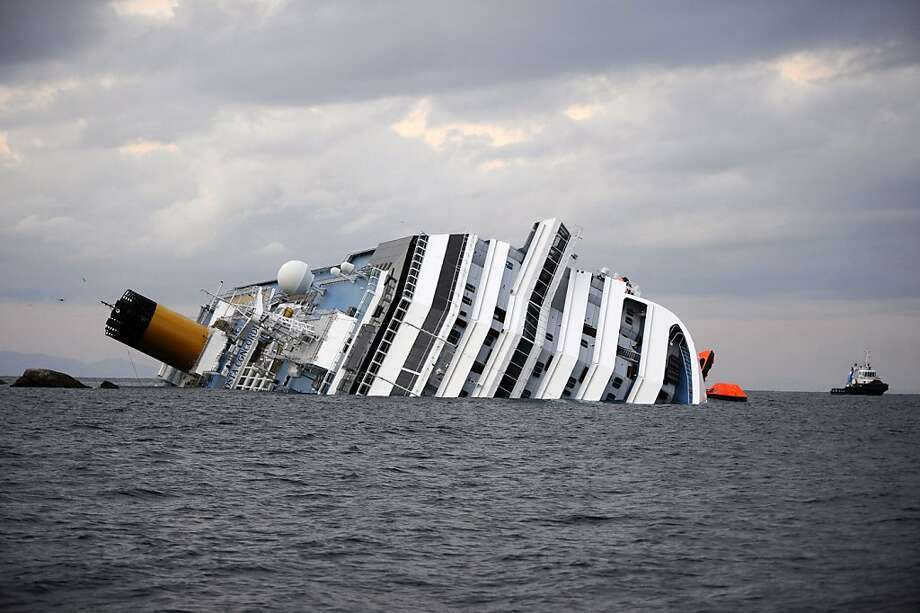 The Costa Concordia cruiseship lies on January 15, 2012 in the harbor of the Tuscan island of Giglio after it ran aground and keeled over off the Isola del Giglio after hitting underwater rocks on January 13. Two South Korean honeymooners and an Italian crewman were rescued today from a cruise ship wreck in Italy but emergency services found another two bodies, bringing the death toll to five. More than a dozen people are still missing after the luxury liner, carrying more than 4,200 passengers and crew, hit rocks just off the Tuscan island of Giglio on the evening of January 13.  AFP PHOTO / FILIPPO MONTEFORTE (Photo credit should read FILIPPO MONTEFORTE/AFP/Getty Images) Photo: Filippo Monteforte, AFP/Getty Images