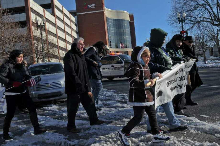 "Qwashanaye Lennon, 8, of Schenectady, center, helps to carry a banner at the head of an annual march honoring the late Dr. Martin Luther King, Jr. on State Street and adjacent streets outside the First United Methodist Church on Sunday Jan. 15, 2012 in Schenectady, NY. Assemblyman James Tedisco is to the left of her. A program titled ""Celebrating Local Leaders: Courage and Commitment in the Spirit of Dr. Martin Luther King, Jr,"" sponsored by the Martin Luther King, Jr. Coalition of the Schenectady County Human Rights Commission was held in the church after the march.  (Philip Kamrass / Times Union ) Photo: Philip Kamrass / 00016108A"