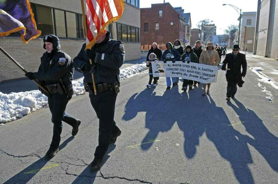 "Schenectady Police officers Mike Crounse, left, and Kevin Maloney, right, carry the city flag and the American flag, respectively, at the head of an annual march honoring the late Dr. Martin Luther King, Jr. on Barrett Street and adjacent streets outside the First United Methodist Church on Sunday Jan. 15, 2012 in Schenectady, NY.  A program titled ""Celebrating Local Leaders: Courage and Commitment in the Spirit of Dr. Martin Luther King, Jr,"" sponsored by the Martin Luther King, Jr. Coalition of the Schenectady County Human Rights Commission was held in the church after the march.  (Philip Kamrass / Times Union ) Photo: Philip Kamrass / 00016108A"
