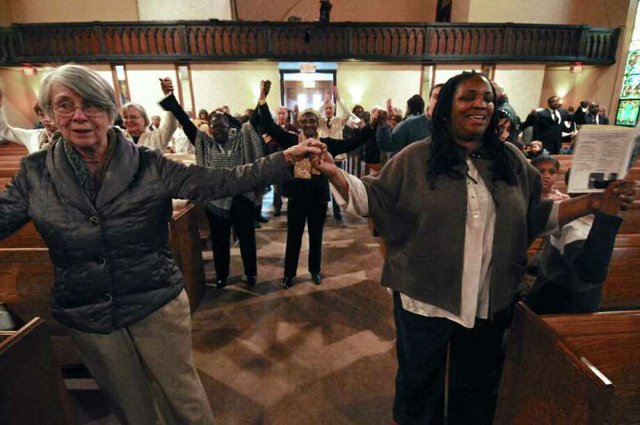 "Meredith Van Vorst of Scotia, left, joins hands with Dr. Deidre Butler of Schenectady, right, while singing ""We Shall Overcome"" during a program titled ""Celebrating Local Leaders: Courage and Commitment in the Spirit of Dr. Martin Luther King, Jr,"" sponsored by the Martin Luther King, Jr. Coalition of the Schenectady County Human Rights Commission, at the First United Methodist Church on Sunday Jan. 15, 2012 in Schenectady, NY. A short march on nearby streets preceded the annual celebration of the late civil rights leader. (Philip Kamrass / Times Union ) Photo: Philip Kamrass / 00016108A"