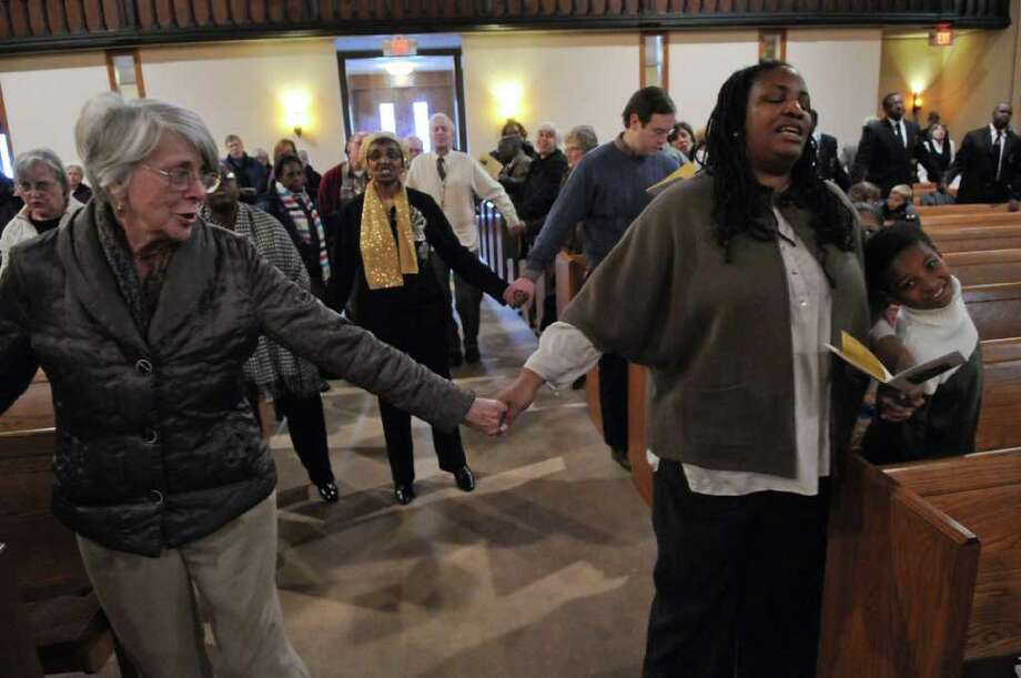 "Meredith Van Vorst of Scotia, left, joins hands with Dr. Deidre Butler of Schenectady, and her son Emmanuel, 7, while singing ""We Shall Overcome"" during a program titled ""Celebrating Local Leaders: Courage and Commitment in the Spirit of Dr. Martin Luther King, Jr,"" sponsored by the Martin Luther King, Jr. Coalition of the Schenectady County Human Rights Commission, at the First United Methodist Church on Sunday Jan. 15, 2012 in Schenectady, NY. A short march on nearby streets preceded the annual celebration of the late civil rights leader. (Philip Kamrass / Times Union ) Photo: Philip Kamrass / 00016108A"
