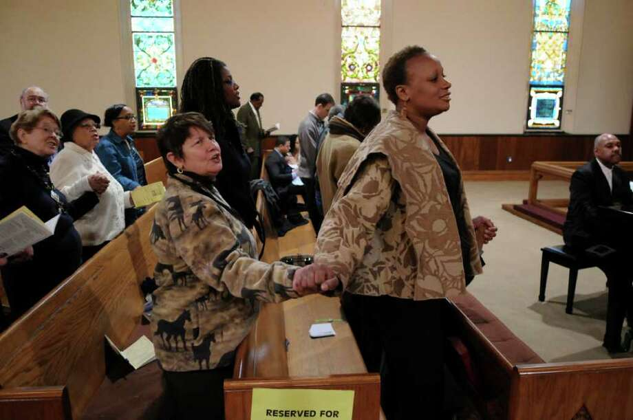 "Sharon Carter, left, joins hands with Shai Butler, right,  both of Schenectady, while singing ""We Shall Overcome"" during a program titled ""Celebrating Local Leaders: Courage and Commitment in the Spirit of Dr. Martin Luther King, Jr,"" sponsored by the Martin Luther King, Jr. Coalition of the Schenectady County Human Rights Commission, at the First United Methodist Church on Sunday Jan. 15, 2012 in Schenectady, NY. A short march on nearby streets preceded the annual celebration of the late civil rights leader. (Philip Kamrass / Times Union ) Photo: Philip Kamrass / 00016108A"